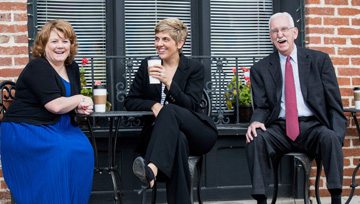 three business people sitting outside at a cafe table