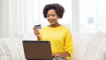 woman holding a credit card while using a laptop computer