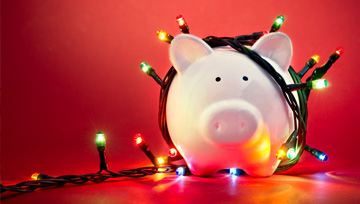 piggy bank wrapped up with Christmas lights